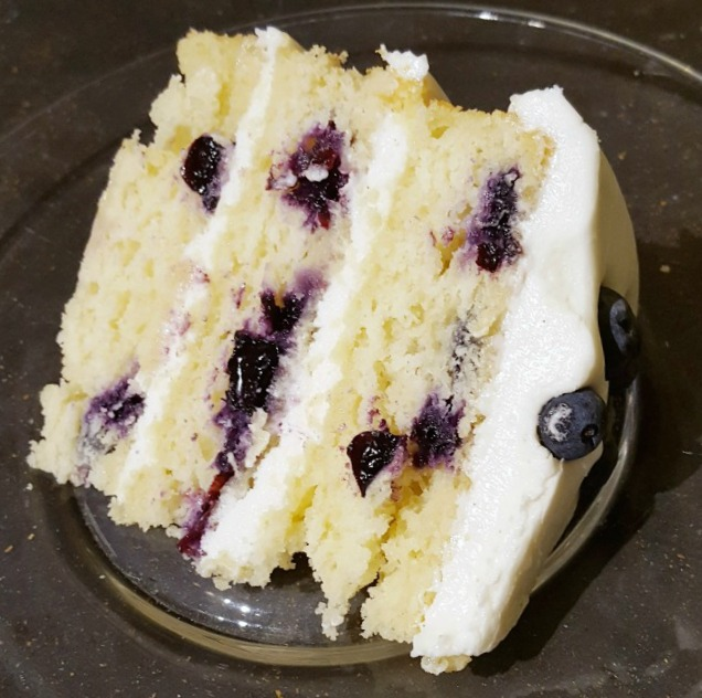 Slice of 3 layered lemon blueberry cake with lemon cream cheese frosting on plate ready to eat.