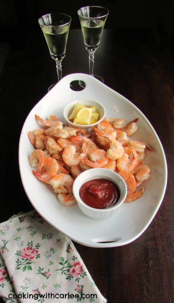 serving platter filled with roasted shrimp, lemon wedges and cocktail sauce with champagne flutes nearby.