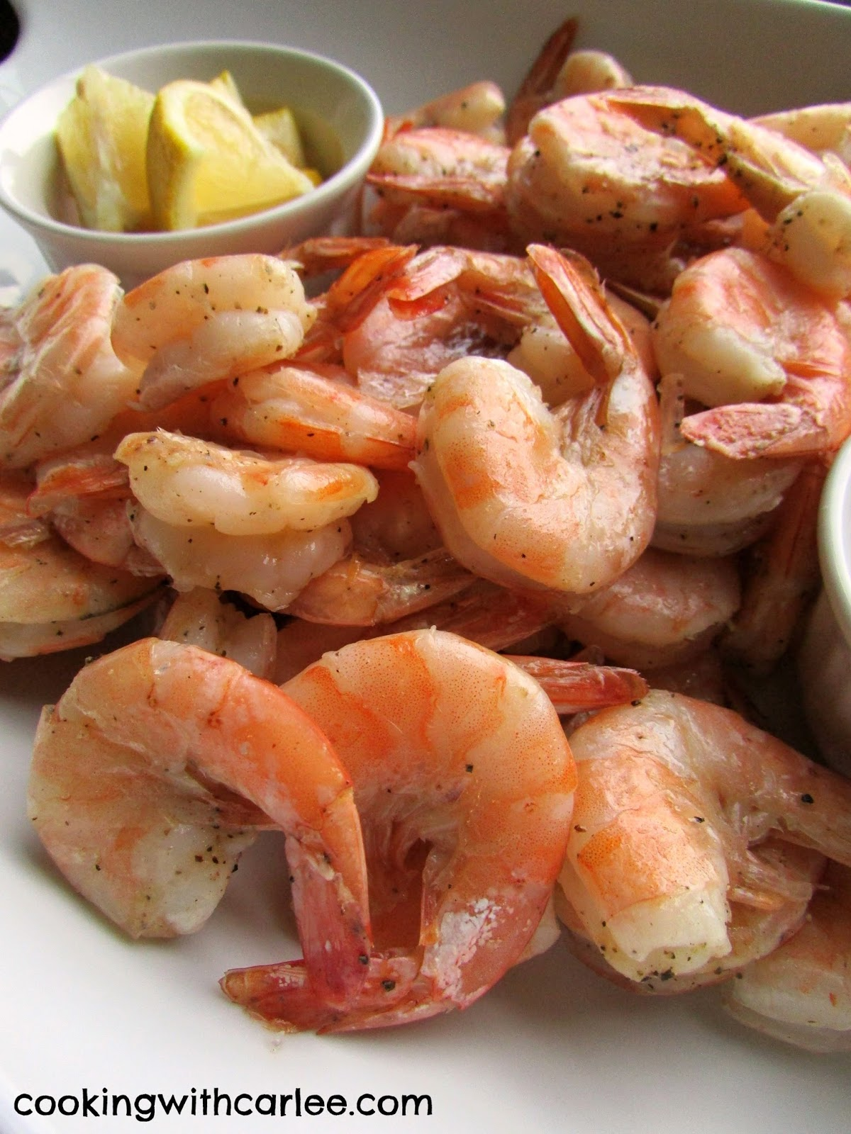 close up of pink roasted shrimp and lemon wedges.
