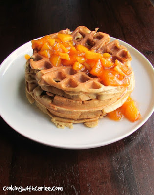 stack of waffles drizzled with cooked peach sauce.