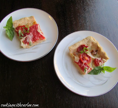 two small square pieces of tomato slab pie with cornmeal crust