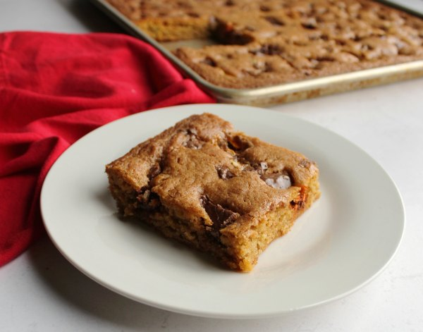 piece of lotsa candy bar blondies on a small dessert plate ready to eat.