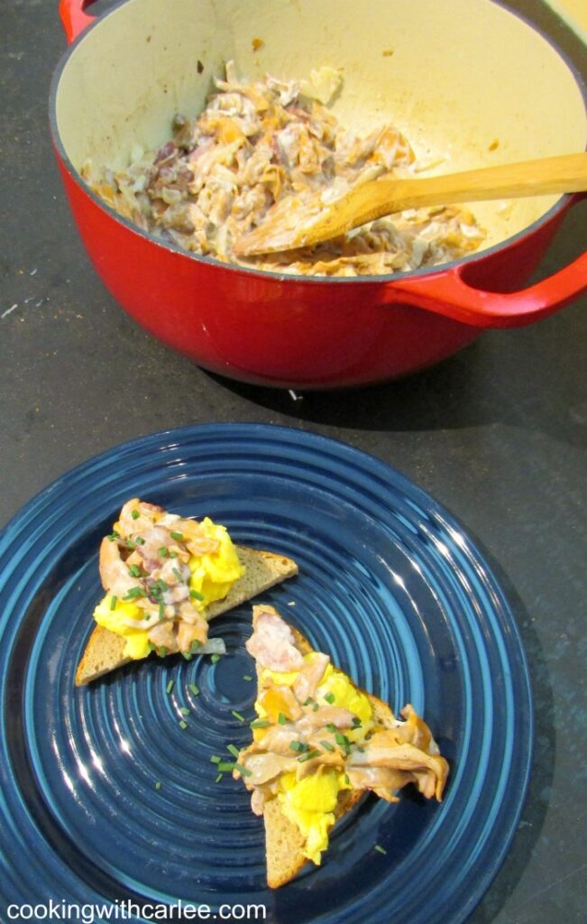 Russian chanterlle mushrooms over eggs and toast with dutch oven of remaining creamy mushrooms in background.