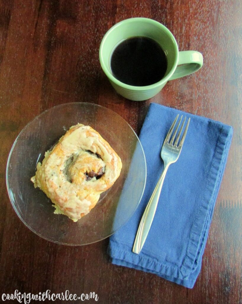 coffee and cream cinnamon roll on plate with cup of coffee and fork nearby.