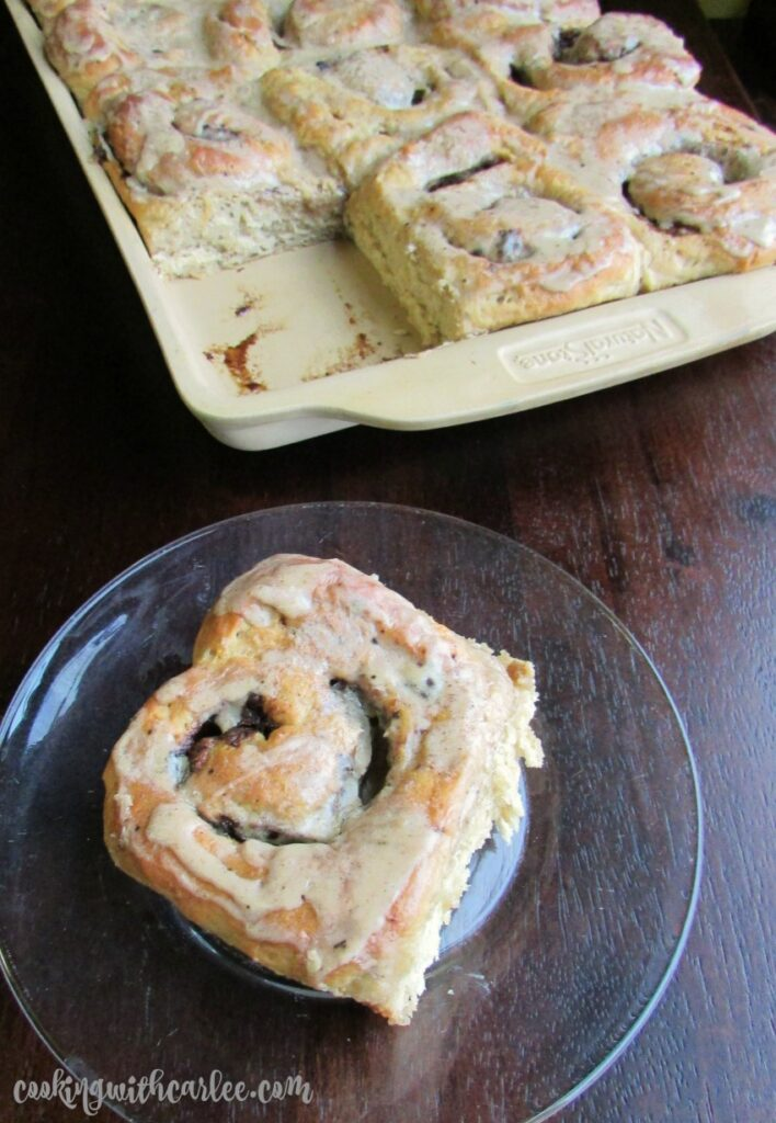 coffee cinnamon roll on plate with tray full of buns in the background.