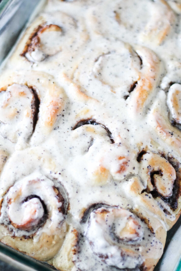 Pan of coffee cinnamon rolls with white icing on top.