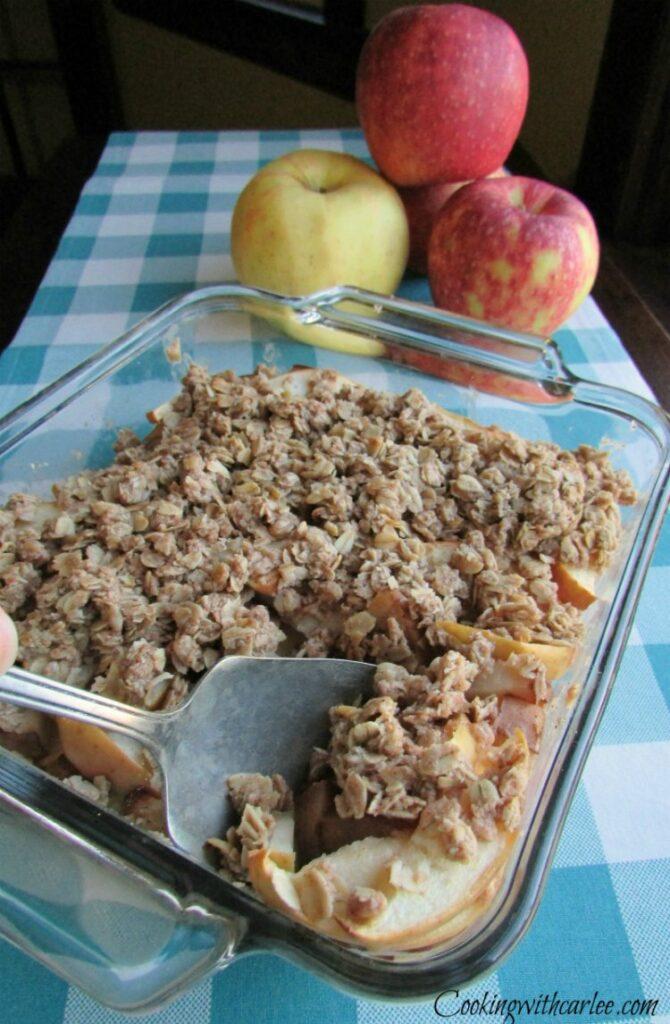 spoon in pan of freshly baked apple crisp.
