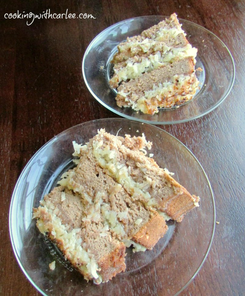 Two slices of German chocolate cake with broiled coconut frosting on glass plates ready to eat.