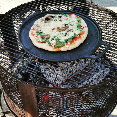 Pizza on cast iron pizza pan cooking over wood fire.