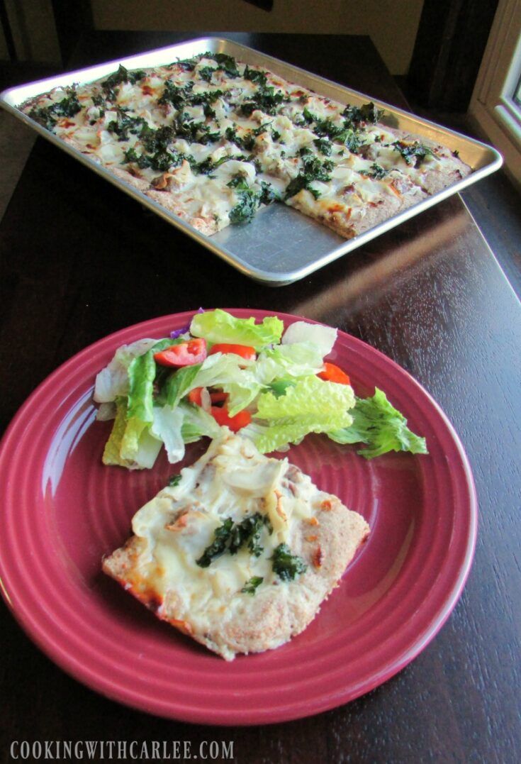 Piece of tuscan pizza on plate with green salad, remaining sheet pan of pizza in background.
