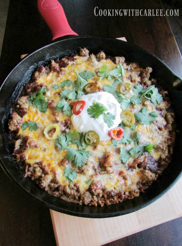 Tamale pie in large cast iron skillet, fresh from the oven with enchilada sauce and melted cheese on top.