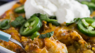 close serving of tamale casserole topped with jalapenos and sour cream, ready to eat.