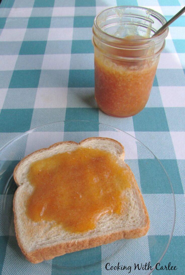 homemade cinnamon peach jam on toast next to jar of jam.