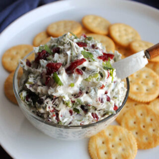 small bowl of cranberry jalapeno cream cheese spread on plate with crackers, ready to eat.