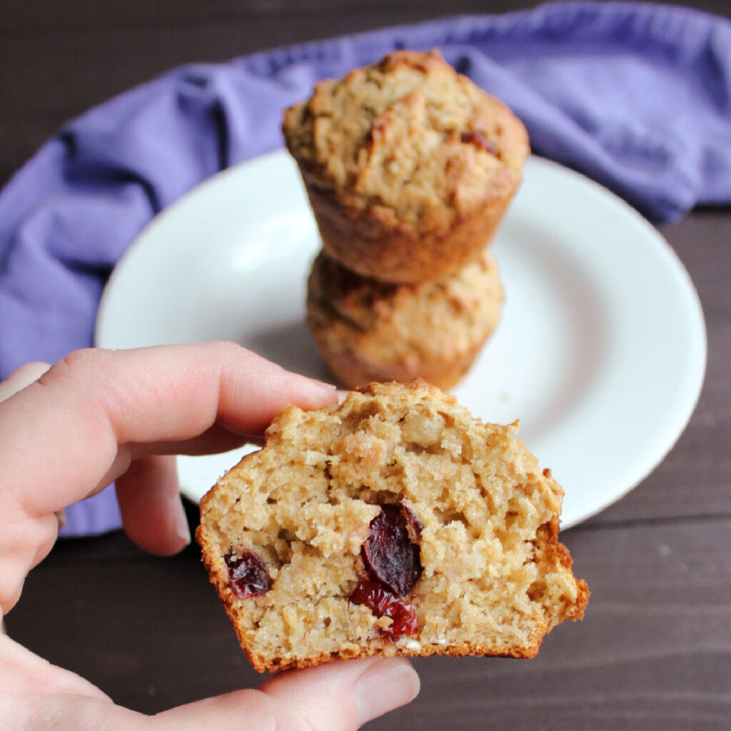 hand holding half of a cranberry oatmeal sourdough muffin