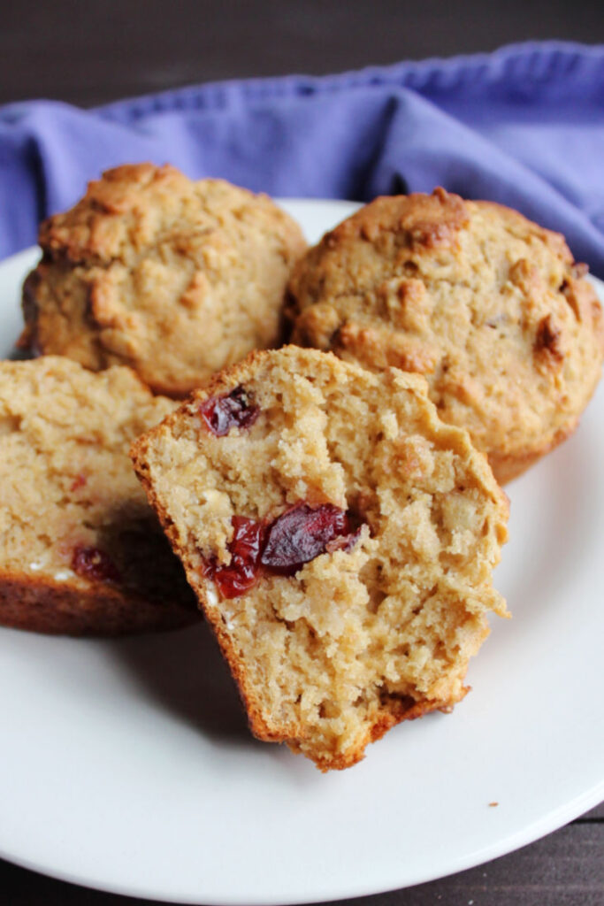 plate of muffins showing the soft inside of one with cranberries