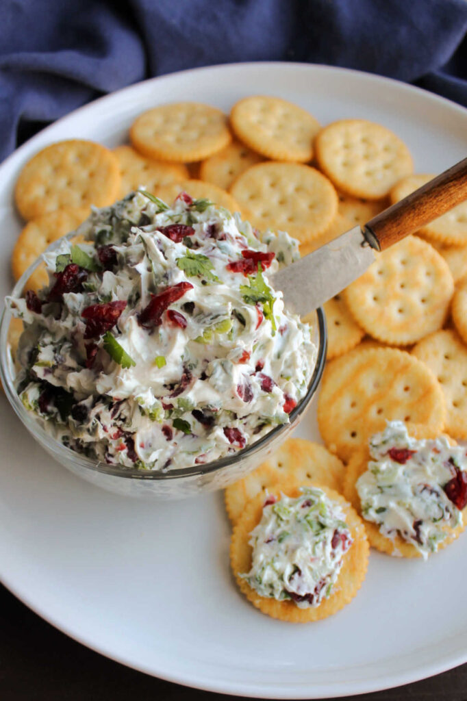 Bowl of jalapeno cranberry cream cheese cracker spread on plate with butter crackers ready to be served.