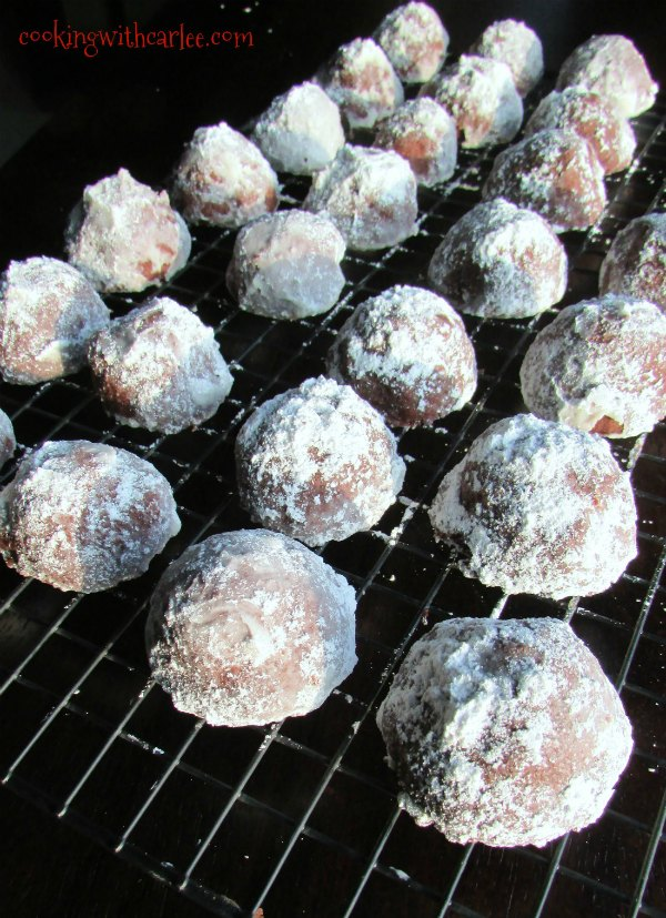 chocolate covered cherry snowball cookies on a cooling rack.