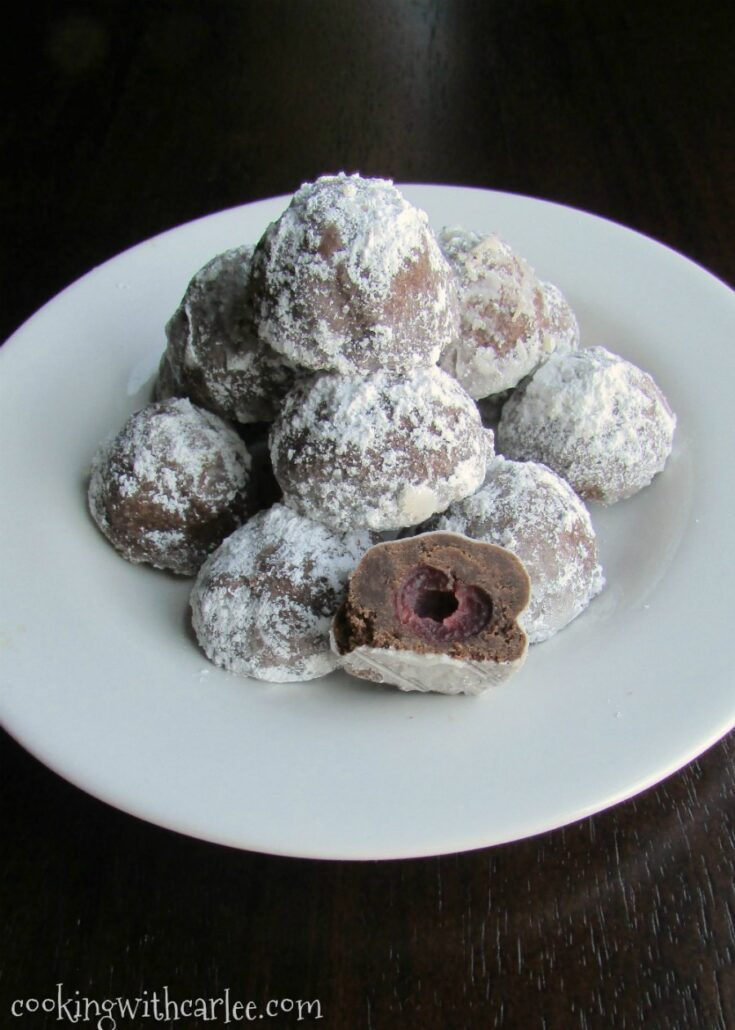 Plate of chocolate covered cherry cookies dusted in powdered sugar.