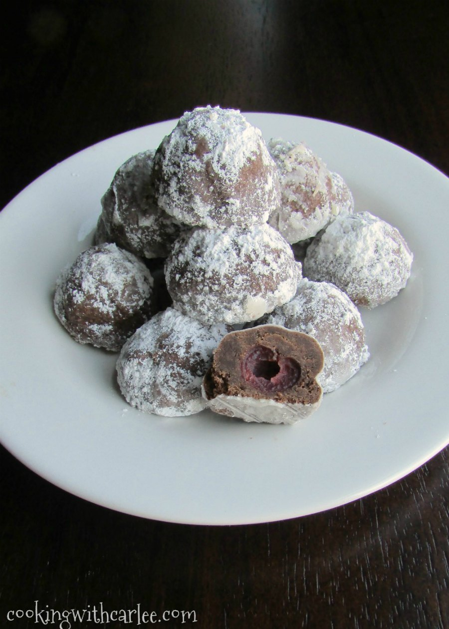 plate full of powdered sugar covered chocolate cookies with a cherry in the middle
