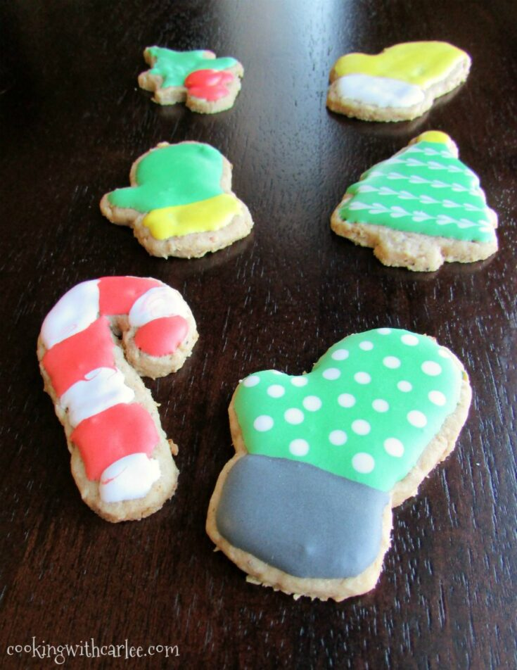 toasted oatmeal cookies cut in mitten, candy cane and Christmas tree shapes with colorful royal icing on top.
