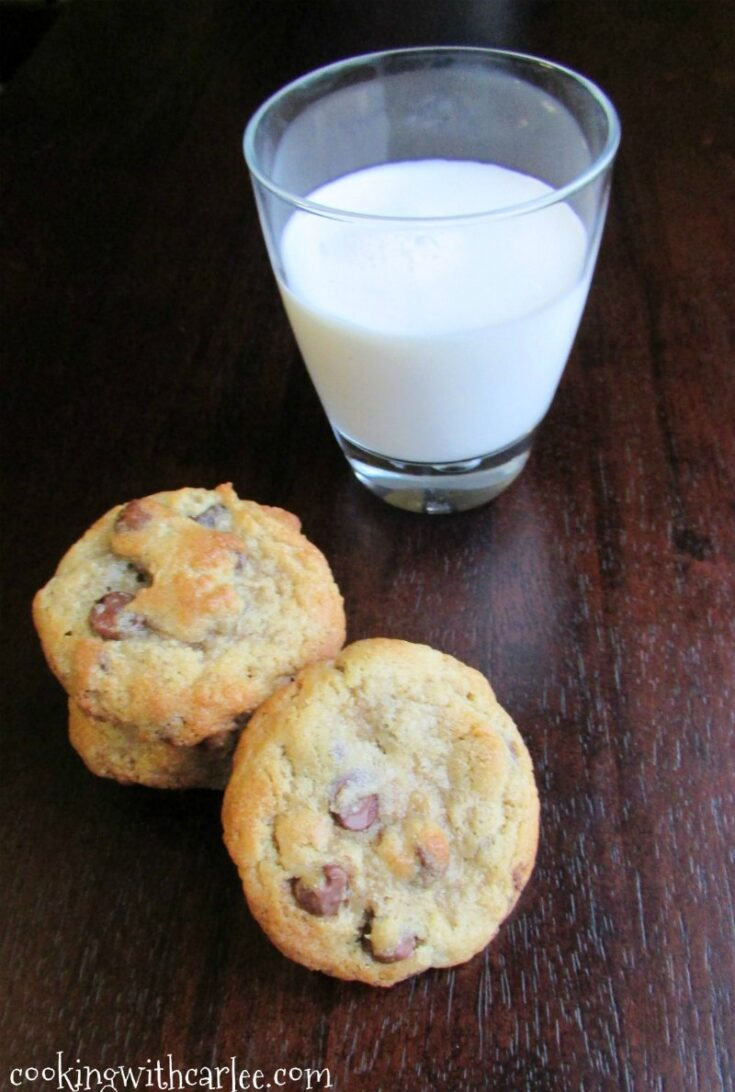stack of chocolate chip cookies next to glass of milk.