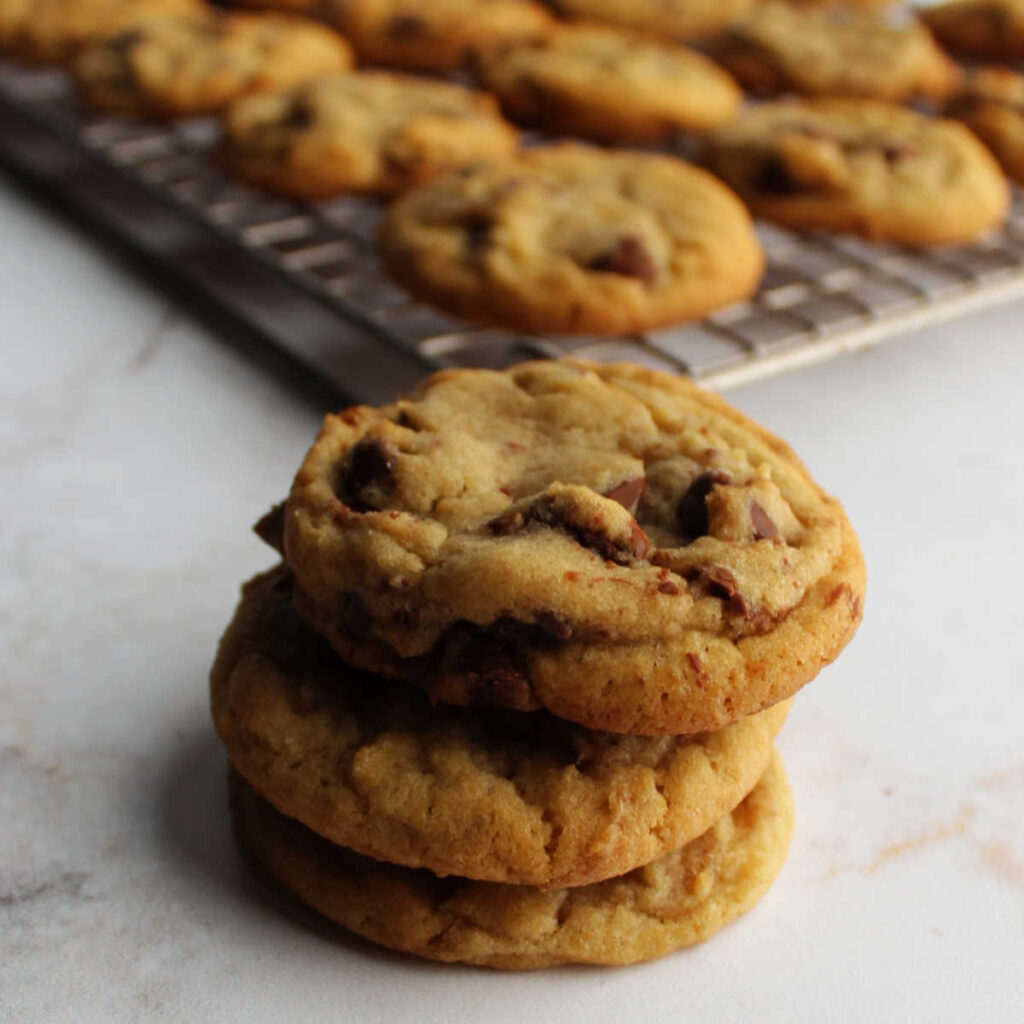 Stack of chocolate chip cookies in front of cooling rack of cookies.