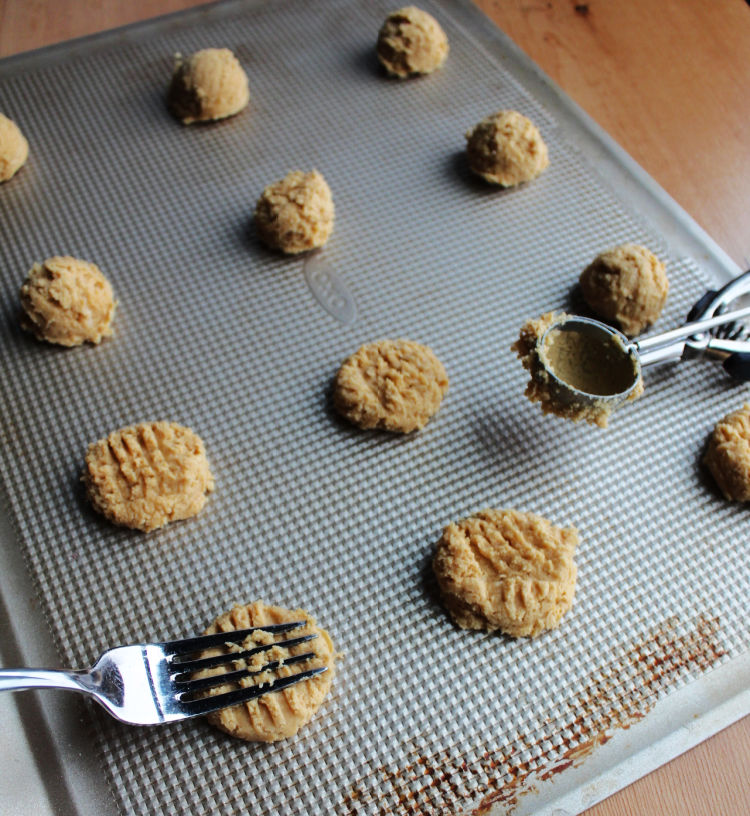 cookie tray with small cookie scoop, balls of dough, and fork putting cross hash in peanut butter cookie dough balls