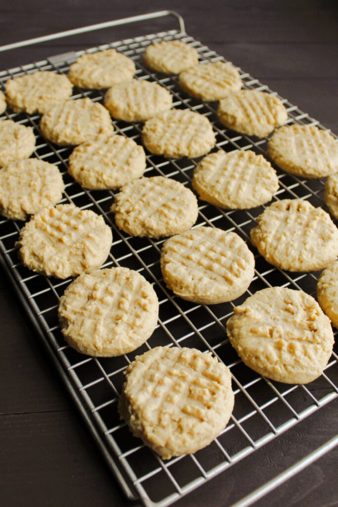 cooling rack filled with soft peanut butter cookies with fork marks on them