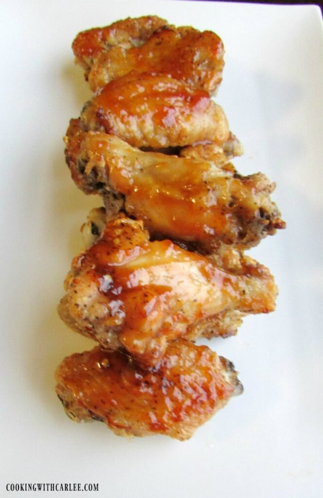 peach habanero chicken hot wings lined up on white background.