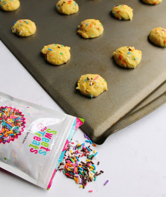 scoops of funfetti cake mix cookies on baking sheet with extra sprinkles nearby