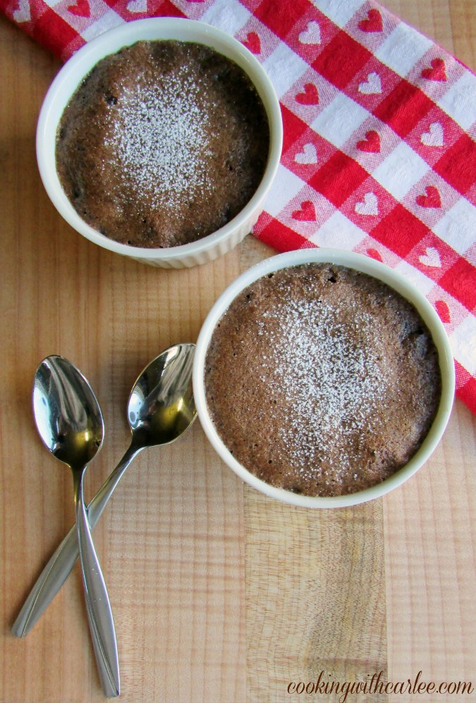 two ramekins of surprise inside baked chocolate pudding dusted with powdered sugar with spoons and heart napkin nearby