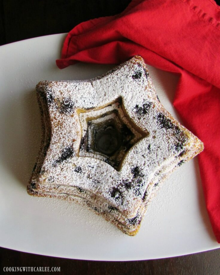 blueberry bundt cake in the shape of a star with dusting of powdered sugar on top.