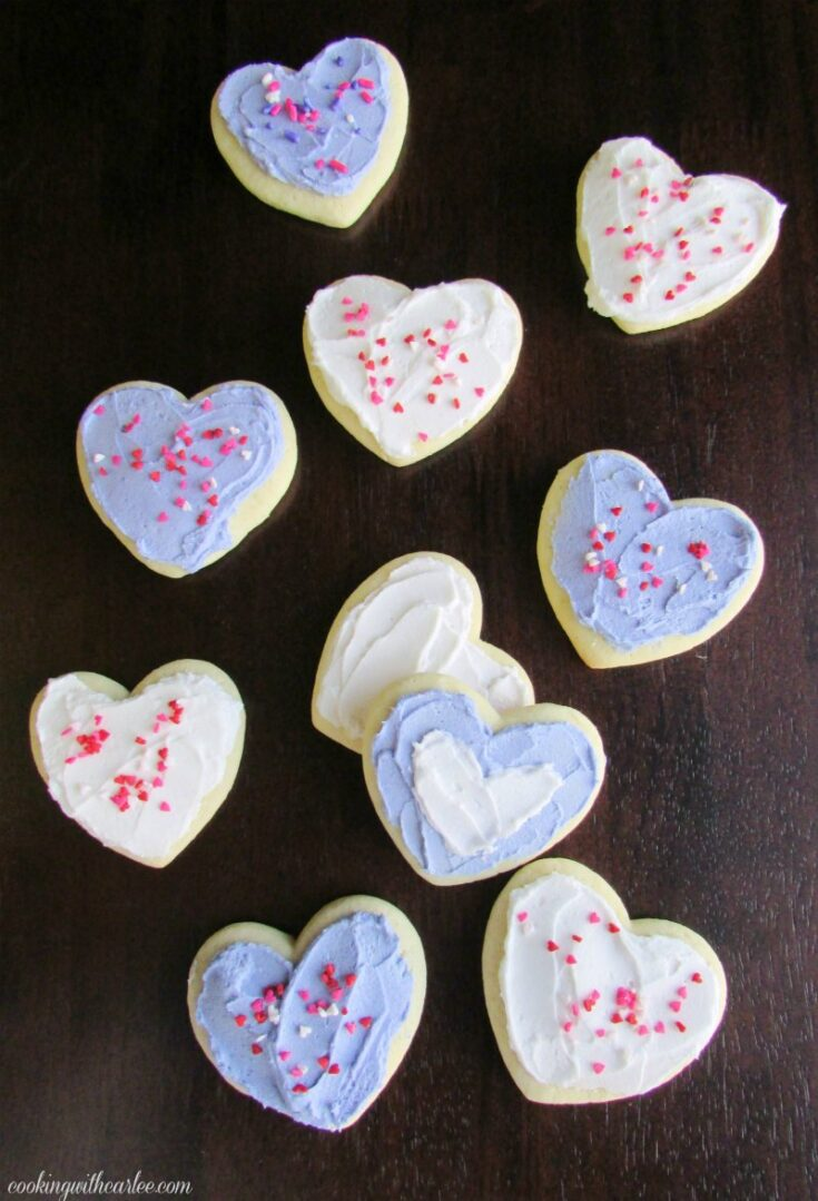 heart shaped sour cream cookies with white and lavender buttercream and sprinkles on top.