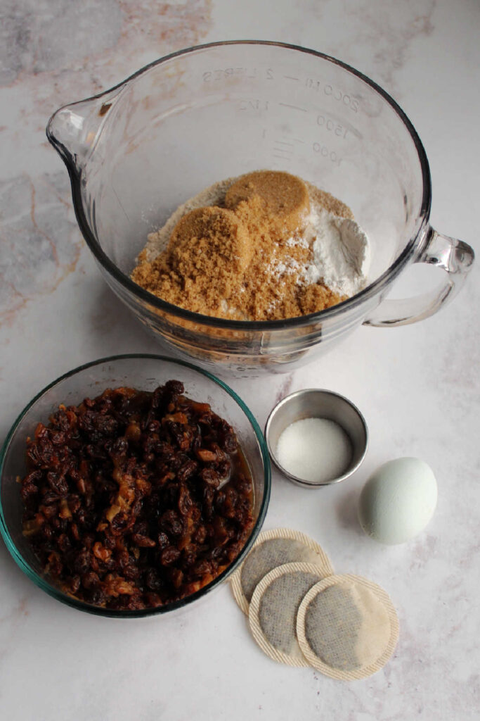 Irish tea brack ingredients including bowl of flour and sugar, raisins and dates soaking in tea, tea bags, sugar and an egg ready to be made into batter.