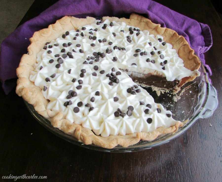 whipped cream topped chocolate pudding pie with slice missing