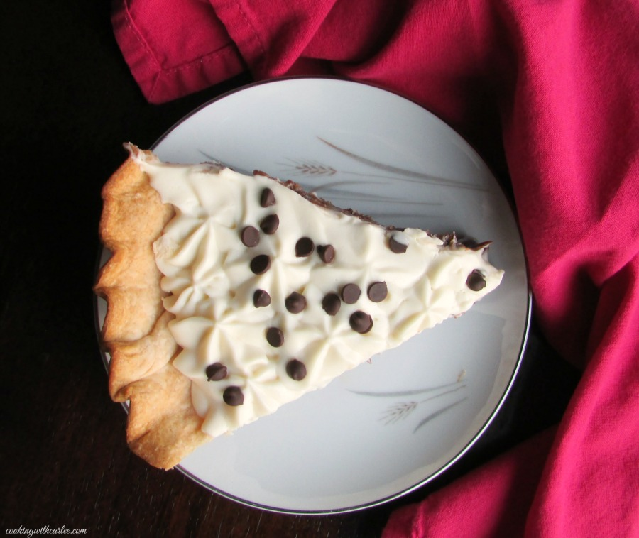 looking down on slice of chocolate pudding pie with stars of whipped cream and mini chocolate chips on top.