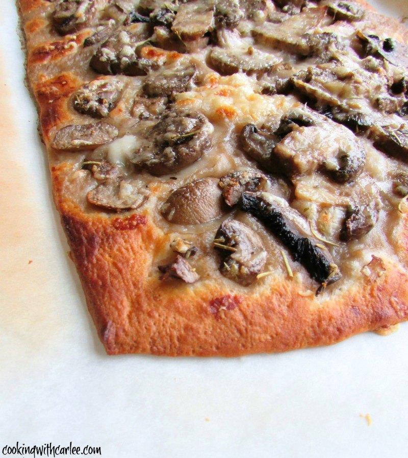 corner of golden brown garlic mushroom flatbread fresh from oven.