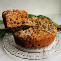 First slice of Irish tea brack being lifted out of round cakelike loaf, showing lots of fruit in the interior.