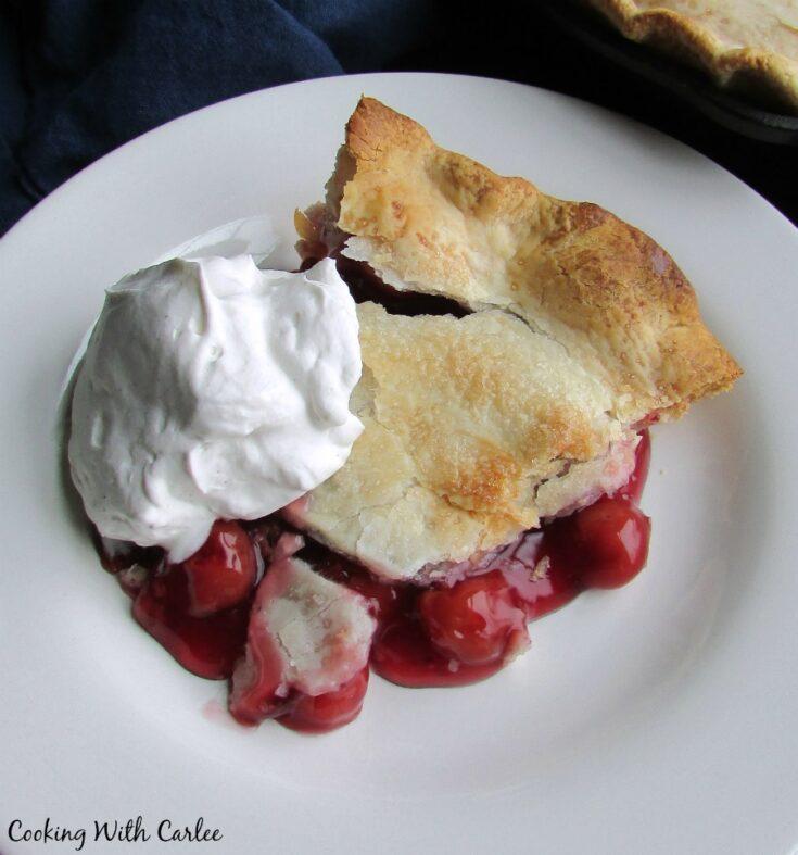 slice of tart cherry pie with whipped cream.