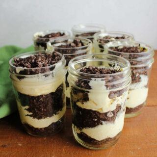 Layers of vanilla pudding mixture and chocolate oreo crumbs layered in jars to make dirt pudding.