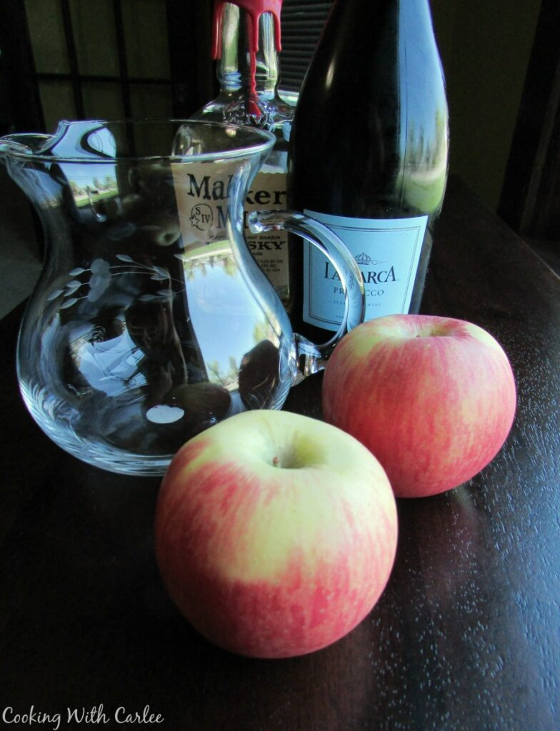 apples, pitcher, bottle of prosecco, bottle of bourbon.
