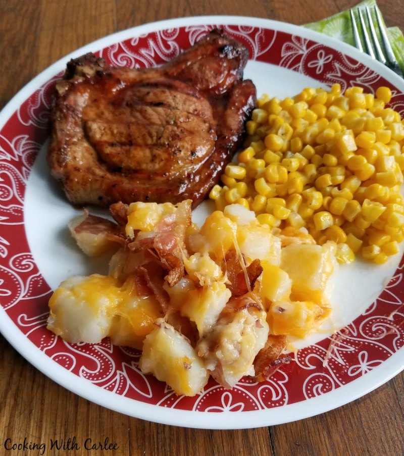 Plate of cheesy potatoes with bacon, bbq pork chop and corn ready to eat.