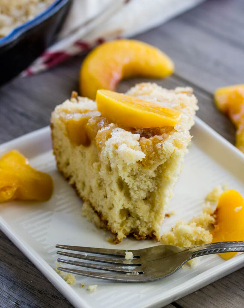 piece of peach coffee cake with extra peaches on plate with fork.