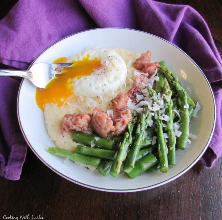 fork breaking yolk over parmesan polenta brunch bowl.