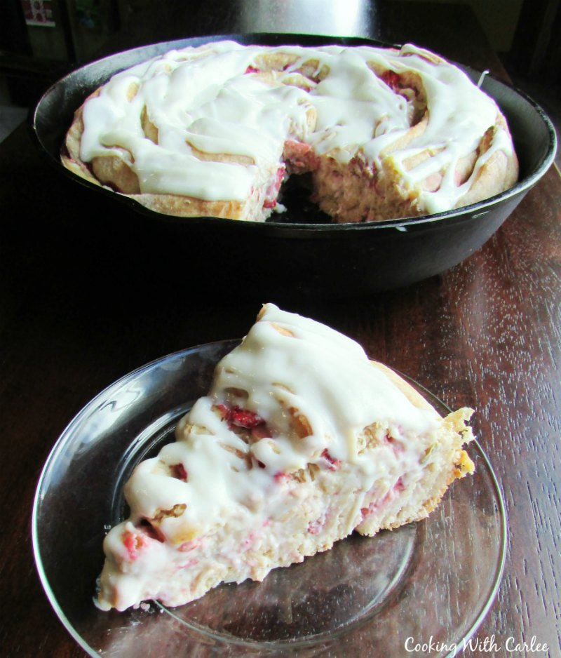 slice of strawberry cinnamon roll with large cast iron skillet behind it.