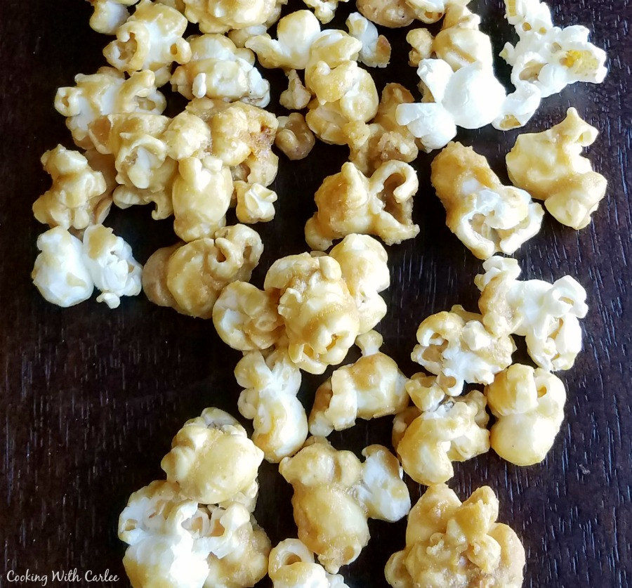 crunchy caramel corn spilled on dark background.