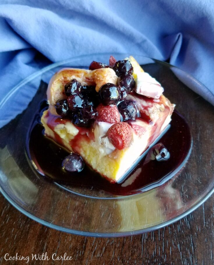 breakfast plate filled with sweet casserole and berry syrup.