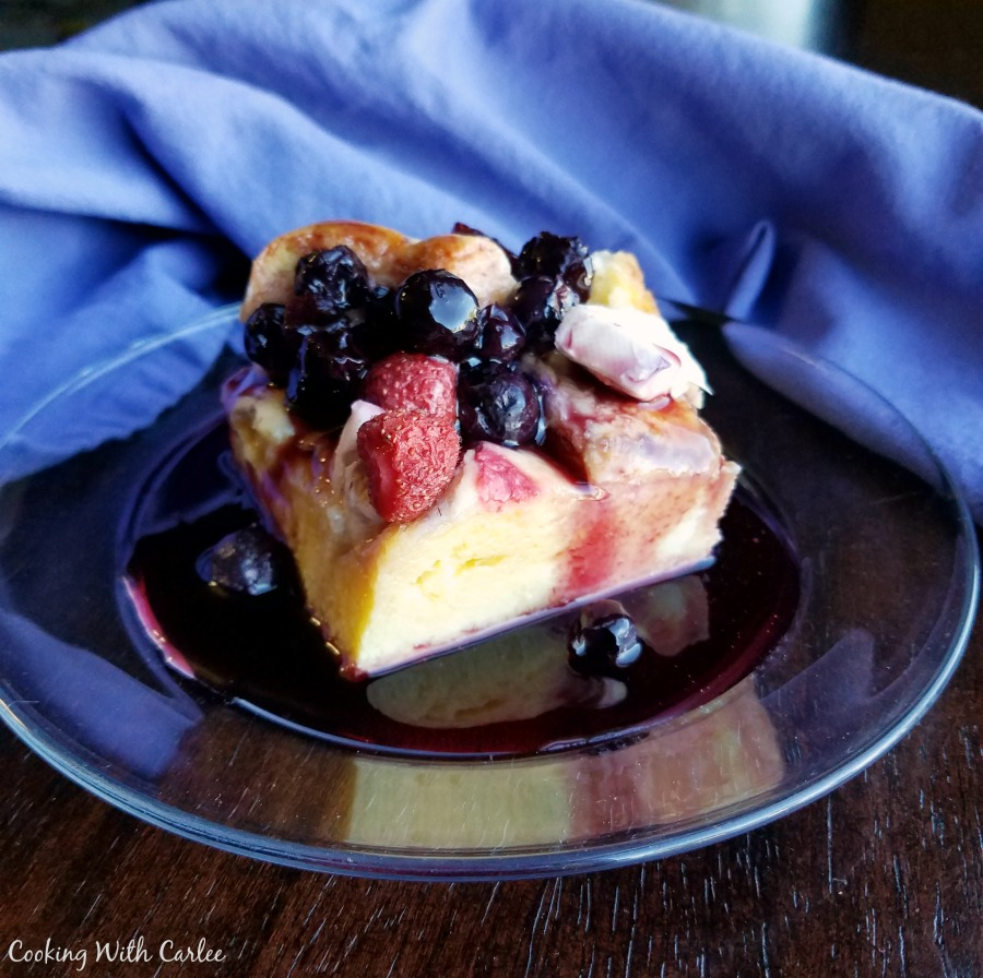 piece of berry and bagel french toast casserole with lots of berry syrup