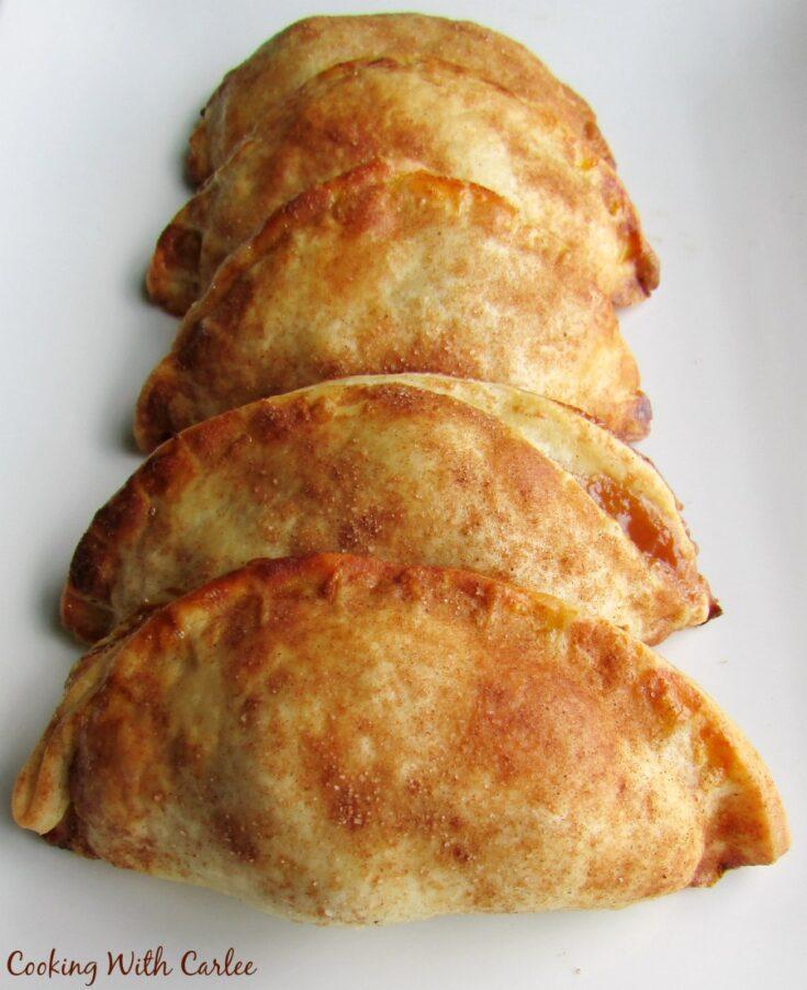 row of cajeta and apple empanadas on plate.